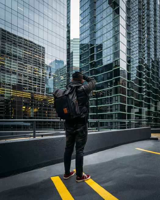 photo of man standing near high rise building